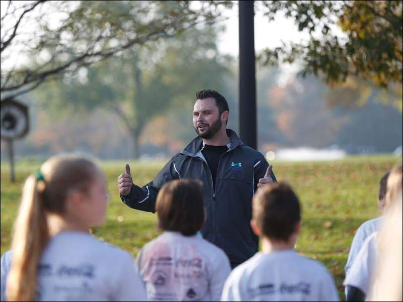 Rob Mahon, a senior program director for the Sylvania Recreation District, leads a group of children in stretching exercises before they race.