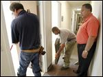 Gary Johnson, who started American Floors & Interiors, supervises his employees Daniel Vasquez, left, and Michael Johnson, right, as they work to put in carpet in the Collier Building on the University of Toledo's Health Sciences Campus.