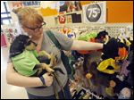 Emily Newman and her dog Fred check out Halloween-themed items for pets being sold at a Dallas store. Owners are projected to spend $350 million for get-ups for their pets.