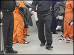 Inmates line up to be moved from booking into other areas of the Lucas County jail.