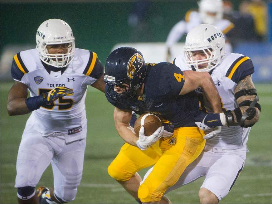 Toledo defender Trent Voss (43), stops Kent State receiver Nick Holley (4) for a five yard loss during the first quarter. Also covering is Toledo defender Ray Bush (55).