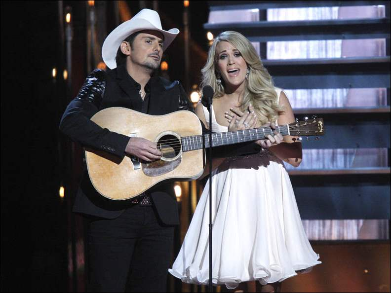 Hosts Brad Paisley, left, and Carrie Underwood perform on stage at the 48th annual CMA Awards at the Bridgestone Arena.