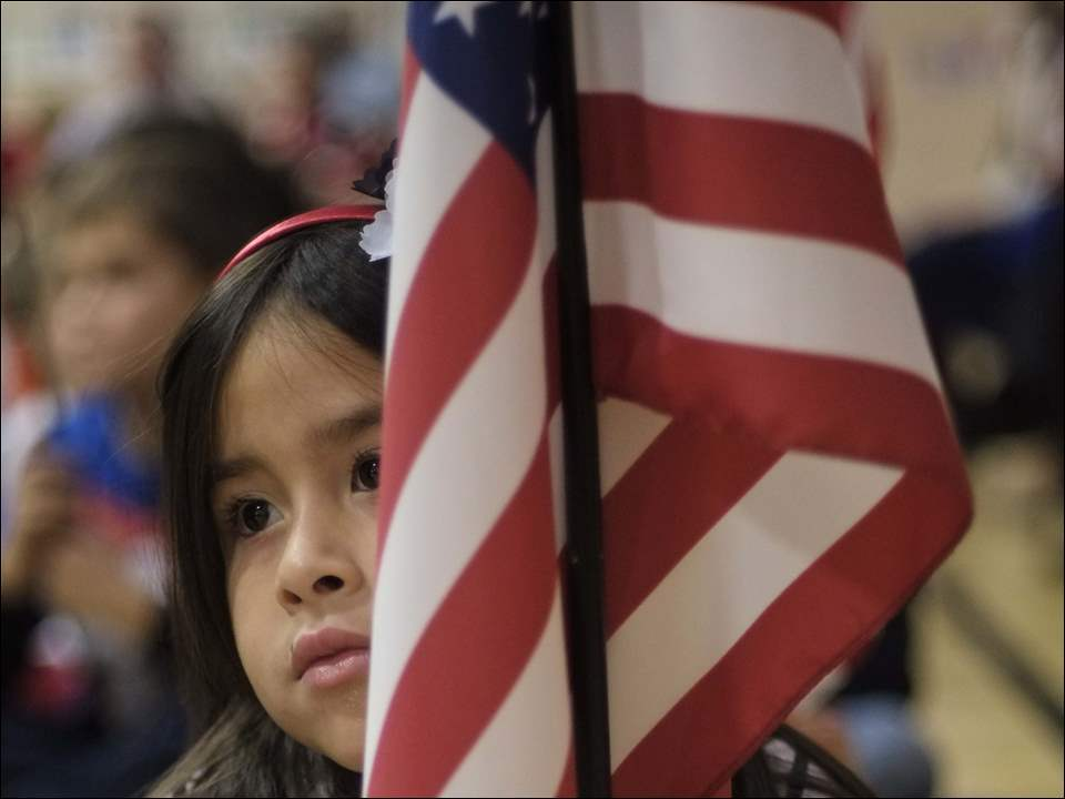Kindergartner Isabella Vazquez holds an American flag.