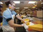 Karen McConaghie cutting blocks of cheese for customers at The Andersons in Toledo Saturday.