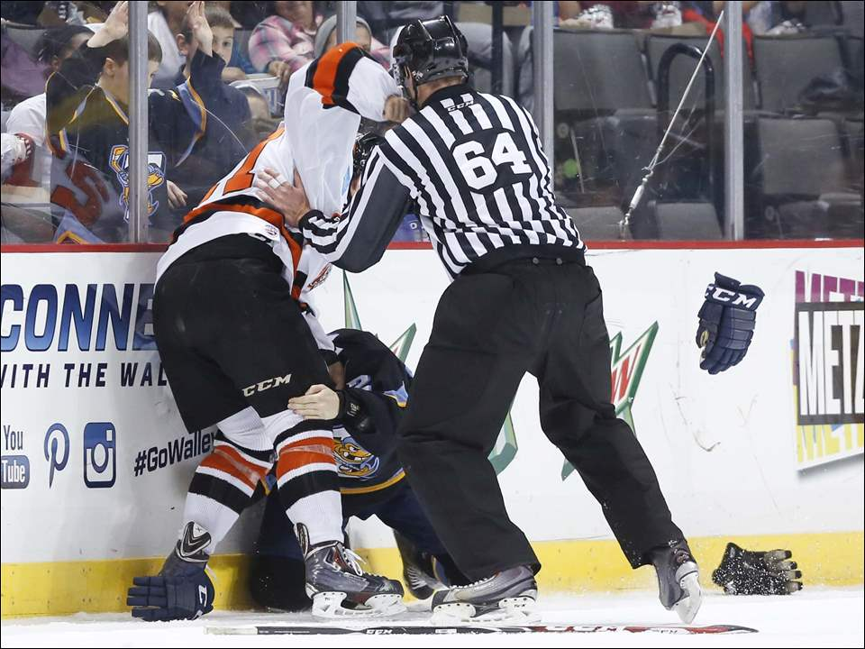 Toledo Walleye Josh Holmstrom (22) gets the worst of a fight with Fort Wayne Komets player Shawn Szydlowski (27) during the first period.