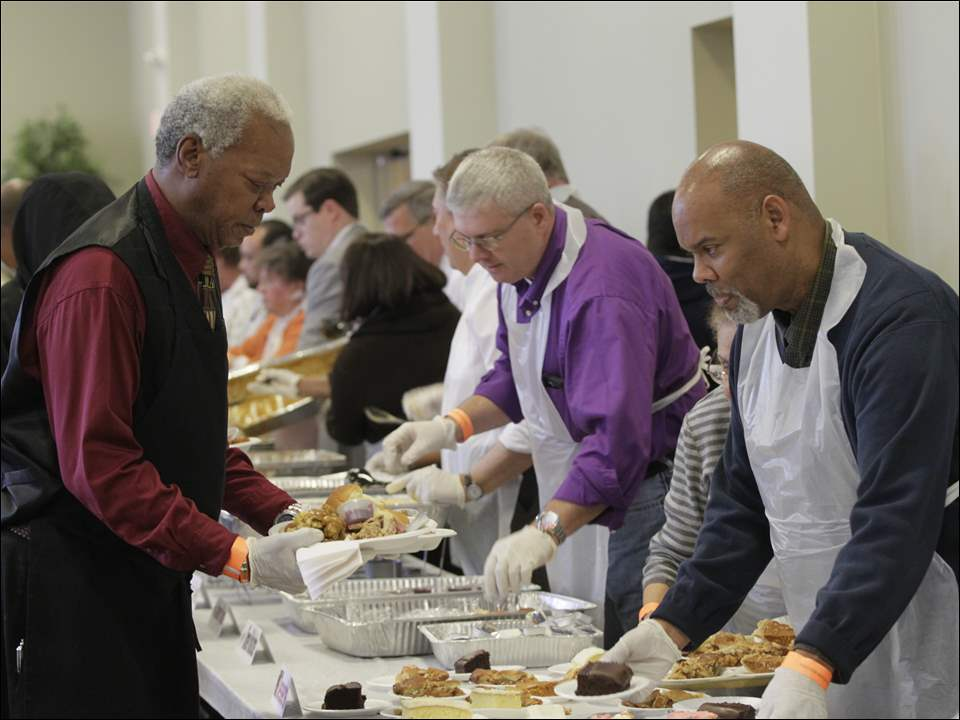 Brian Jackson, of the Glass City Church of Christ, left, gets meals to carry for guests who are unable to be in the line. Center, bending over and wearing glasses, is Tom Bonnington, executive director, Toledo-Lucas County Homelessness Board, and Larry Anderson, of the City's Department of Neighborhoods, right.