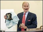On Capitol Hill in Washington, Sen. Bill Nelson (D., Fla.) displays the parts of a defective airbag made by Takata of Japan that have been linked to deaths in cars driven in the United States.