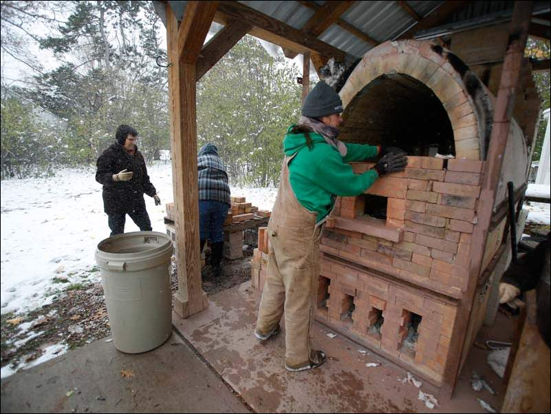 "Christy Cordell, right, a pottery assistant from Oregon, ""unbricks"" the wood kiln after the pottery has been fired for over 16 hours using a quart of wood on the last run of the wood kiln. Students Stephanie Cavanaugh, left, from Bowling Green, and Pat Halicek, center, help stack the bricks."