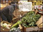 Phil Ciolino, manager of Ciolino Fruit and Vegetable Market in Temperance, stacks produce to be donated for holiday meals at Thomas Temple Church of God in Christ.