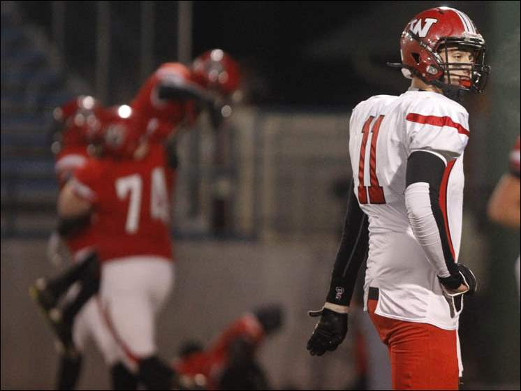 Wauseon's Noah Castle looks away as Kenton's players celebrate a touchdown.