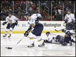 File photo of Toledo Walleye player Jared Nightingale (18) picking up a loose puck as teammate Joel Chouinard (72) and Greenville Road Warriors player Trevor Parkes (19) collide.