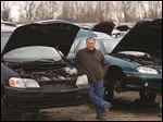 Joel Beren, junkyard owner, and stands amidst a small number of his cars at Cherry Picked Auto Parts.