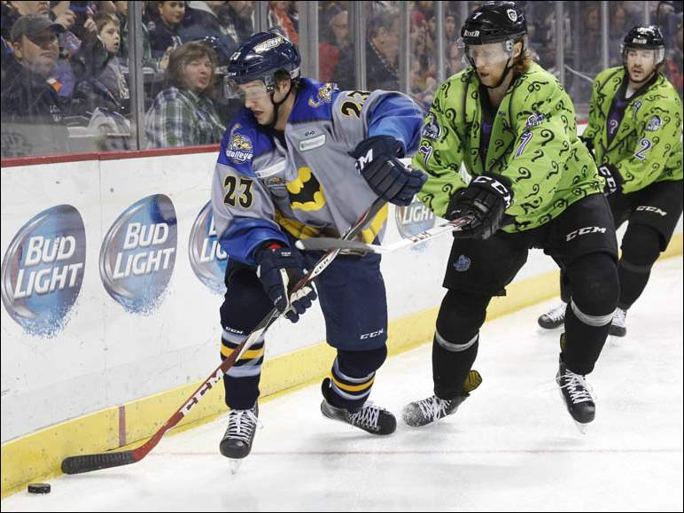 Toledo Walleye player Alden Hirschfeld (23) keeps the puck away from Evansville IceMen player Randy Cure (7).
