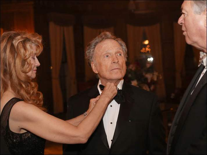 Martha Rogers takes a moment to straighten the bow tie as her husband Dick Cavett speaks with Toledo Club President John Fedderke, right, during the cocktail hour of this year's President's Dinner.