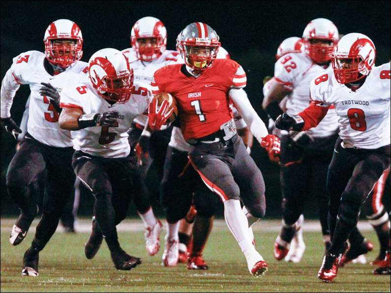 Central Catholic's Tre'€™Von Wade (1) runs ahead of Trotwood-Madison's defenders during the Division III state semifinal.