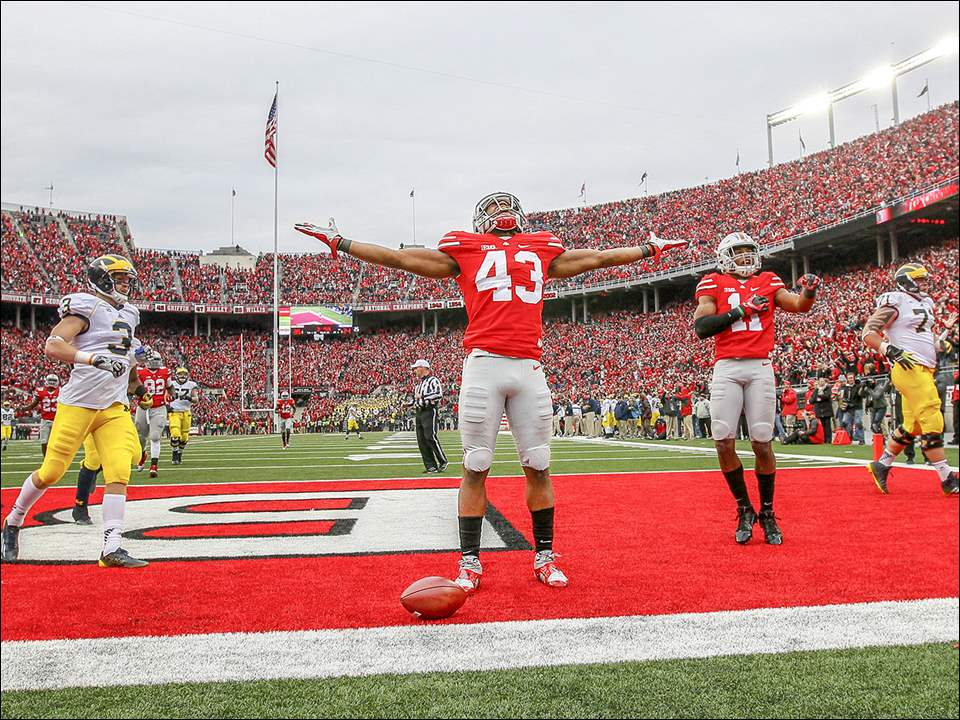 Ohio State University football player Darron Lee (43) celebrates after scoring a touchdown on a fumble recovery against the University of Michigan during the fourth quarter in front of a record crowd at Ohio Stadium, Saturday, November 29, 2014.
