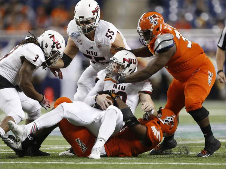 Bowling Green State University players Gabe Martin (11) and Taylor Royster (33) sack Northern Illinois University quarterback Drew Hare (12).