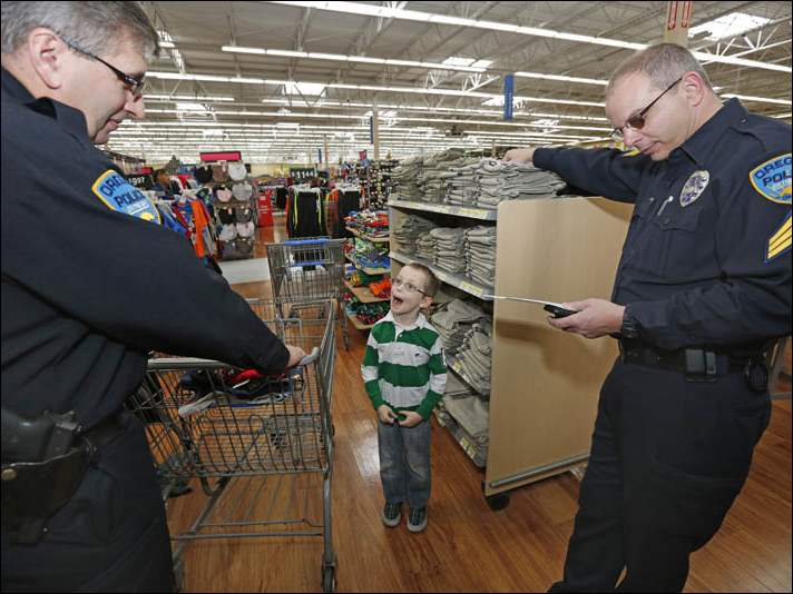 Oregon Police Assistant Chief Paul Magdich, left,  gets a reaction from James Elliott, II, 7, as he tells him about his own son. At right is  Sgt. Doug Iannantuono.