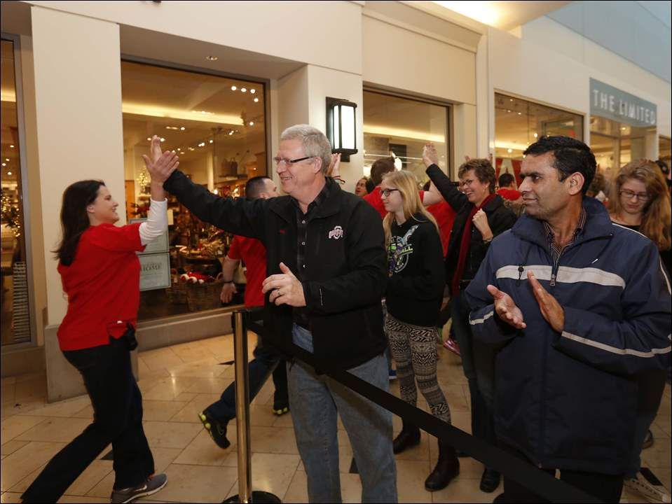 Brian O'Shea, of Sylvania, gives a high five to an Apple store employee before the opening.