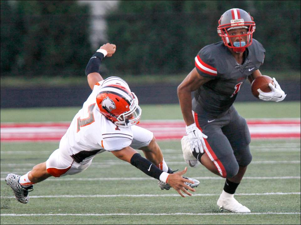 Southview's senior Jay Lawrence (7) is unable to stop Central Catholic's junior TreVon Wade (1) on his run in the first quarter of the Friday, September 5, 2014.