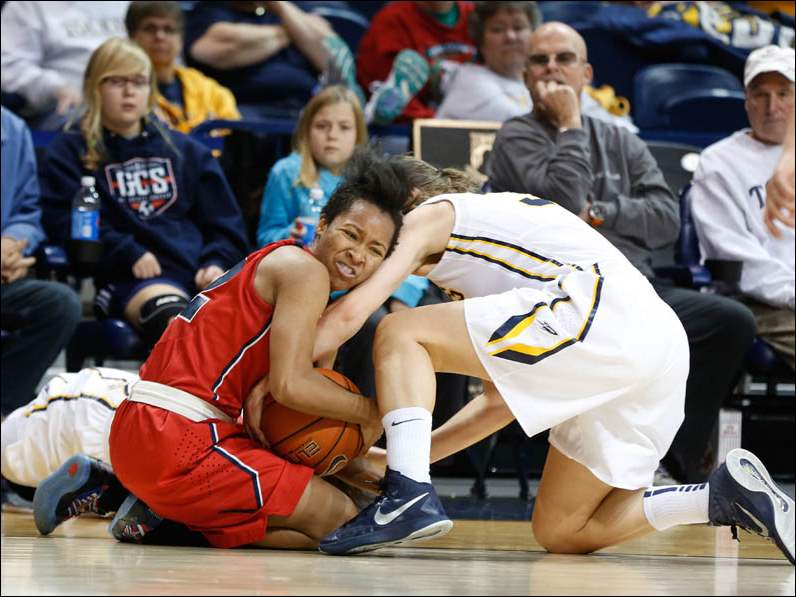 UT's Ana Capotosto, right, and Janice Monakana, rear, tie up UDM's #12, Minisha Frederick-Childress.