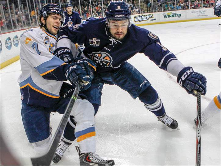 Greenville Road Warriors' Spencer Humphries, right, competes for the puck with Toledo Walleye's Tyler Barnes.