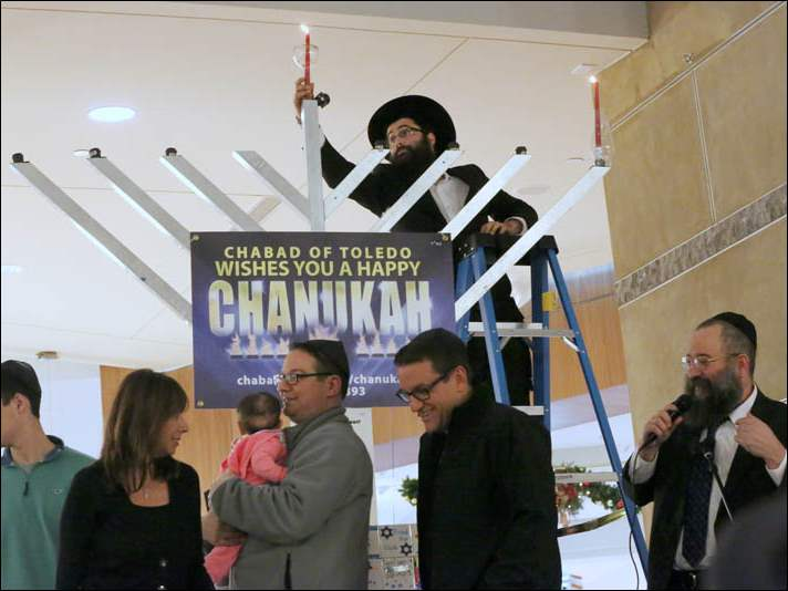 Rabbi Shmouel Matusof, center, places the Shamash candle in the center of Unity Menorah after lighting the far right candle for the first night of Chanukah.