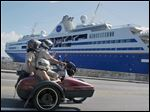 A trio on a motorcycle and sidecar pass the Semester at Sea cruise ship docked in Havana's harbor.