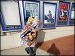 A poster for the movie 'The Interview' is carried away by a worker after being pulled from display in Atlanta.