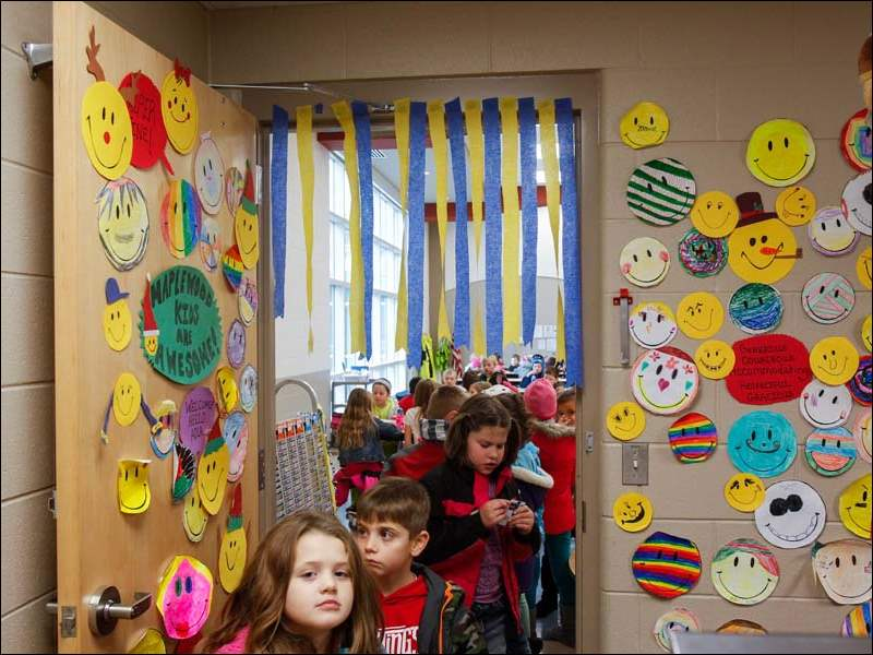Children at Maplewood Elementary School line up for lunch in a room decorated with their smiley drawings at the school.
