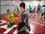 Braden Gandee, 8, left, the first wrestler with Cerebral Palsy to attempt wrestling with the Great Lakes Wrestling Club at Bedford Junior High School works on his balance with his brother Hunter, 15.