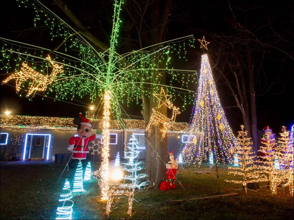 The home of Luke Barron is illuminated during a computer-controlled light display at his home in Temperance, Mich.