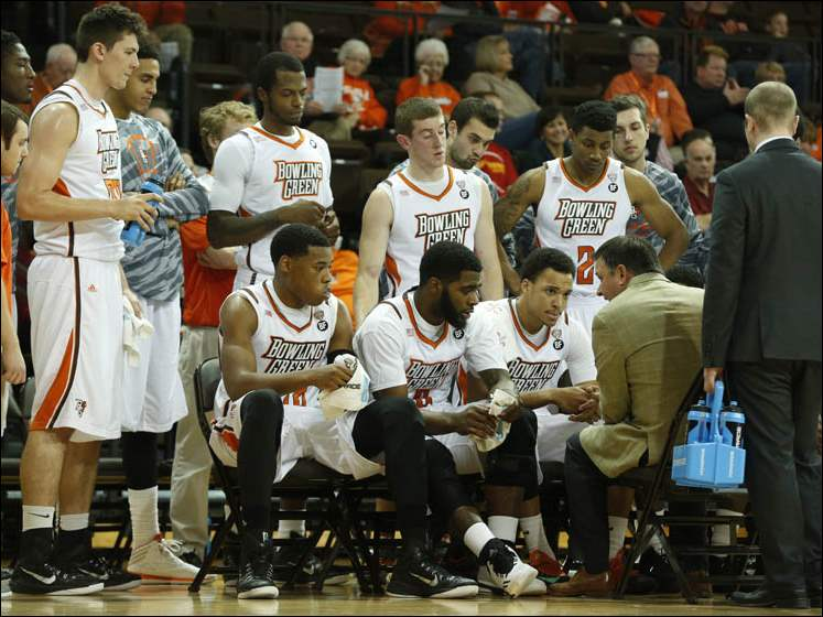 BGSU head coach Chris Jans, seated at right with back to camera, and the team during a time out.