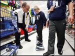 Toledo Police Officer Jason Lenhardt, left, watches as Matt Nickell, 8, tries out a snowboard during the '12 Kids of Christmas' event at Meijer on Tuesday.