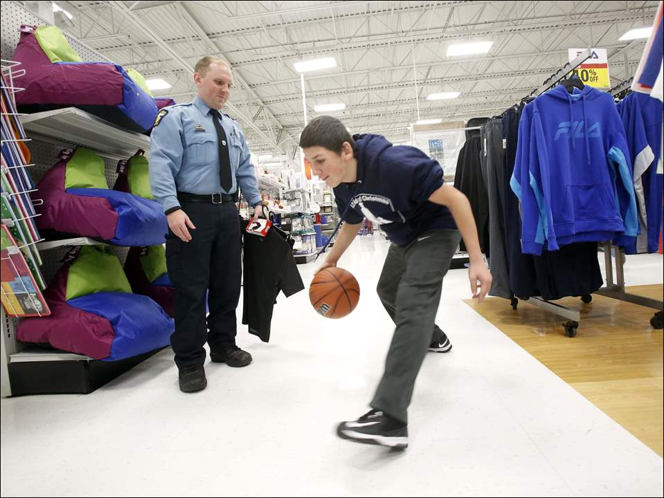 Toledo Police Officer Zack Peterman, left, watches as Austin Bernal, 13, right, tests out a basketball.