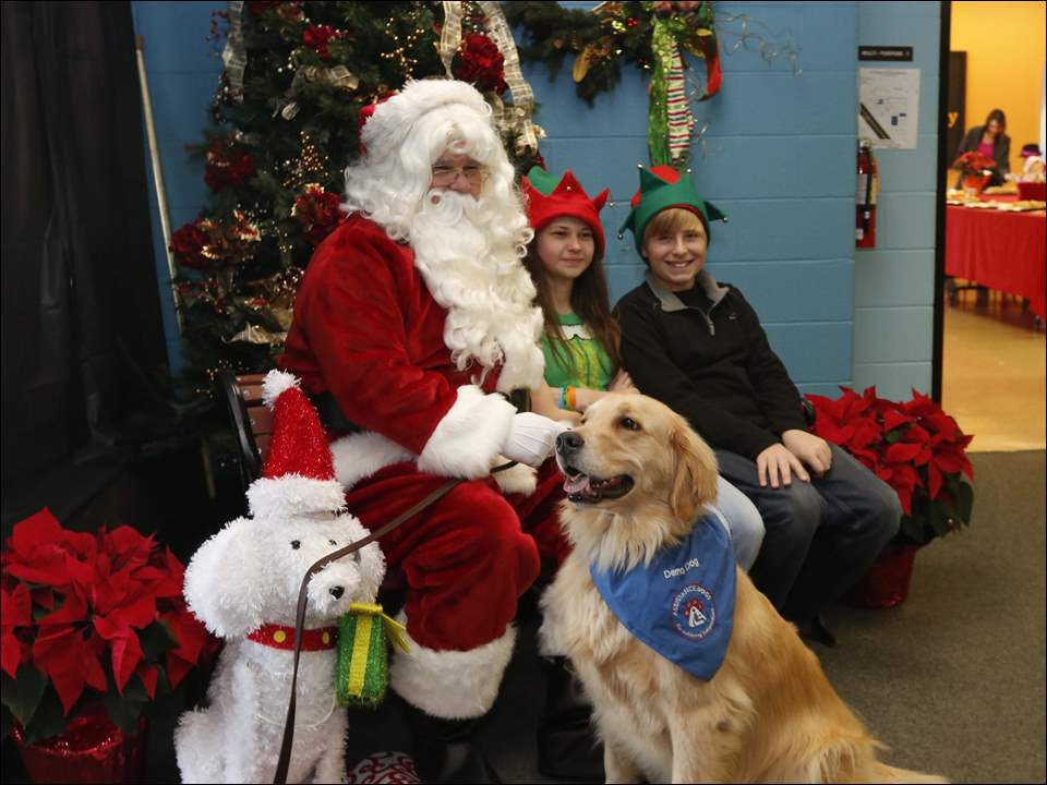 During the Auxiliary to the Ability Center's Children's Christmas party Santa Claus is aided by two elves, Emily Perion and Burton Kozsey, both 13 and both residents of Temperance. With them is Amelia, a demonstration dog for Assistance Dogs of America Inc.