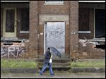 A woman walks past a dilapidated building in East Cleveland.  This impoverished Cleveland suburb is considering filing a municipal bankruptcy, making it the first city in Ohio since bankruptcy laws were established in 1934, to do so.