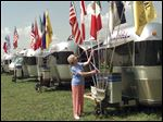 In this 1997 photo, Cathy Laliberte of Billings, Mont., raises the flags on her 25-foot Airstream trailer at an international rally in Huntsville, Ala. Devotees socialize at rallies all over the world and Baby Boomers are the heart of the demographic.