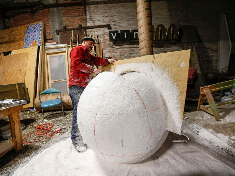 Anthony McCarty scrapes the styrofoam to create the ball shape.