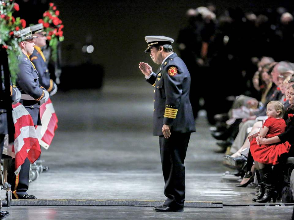 Toledo Fire Chief Luis Santiago salutes the casket of firefighter James Dickman during the Last Alarm funeral service at SeaGate Convention Centre for Mr. Dickman and Stephen Machcinski in January.