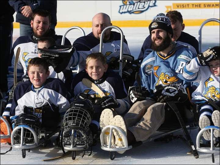Braden Gandee, of Temperance, center, smiles as he is photographed with other members of the sled hockey team the Walleye, along with ECHL Walleye defenseman Cody Lampl, center right, after the match against Perrysburg High School's hockey team.