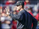 San Francisco coach Jim Harbaugh waves to the crowd before Sunday's game against Arizona.