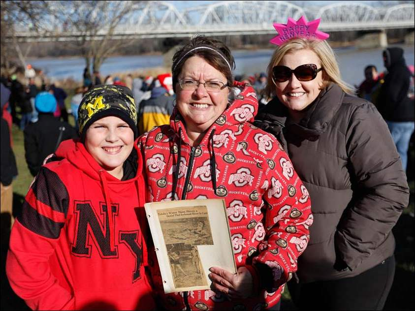Joan Mitchell, center, with her grandson Bradley Strub, 11, and daughter Julie Pesartic, right, holds a photo of her grandmother Cleo Moore taking the plunge in 1928, before the three take part in the Polar Bear Plunge into the Maumee River at Waterville Memorial Park, Thursday.