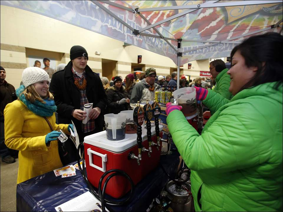 Micaela Dixon, right, pours a Summit Winter Ale for Kathleen Hurley, left, and Cody Clark, right. And, yes, he is wearing a pretzel necklace.