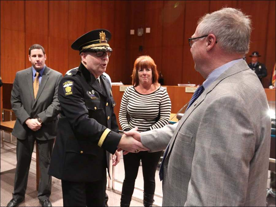 Toledo Police Chief George Kral is congratulated by Toledo Mayor D. Michael Collins after being sworn in.  Looking on are his son George, left, and wife Teresa.