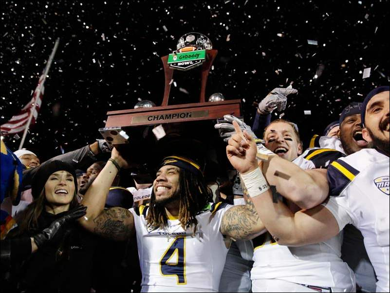 Toledo defensive back Jordan Haden (4) holds up the GoDaddy championship trophy along with teammates and NASCAR driver Danica Patrick at the end of the GoDaddy Bowl Sunday, in Mobile, Ala. Toledo won 63-44.