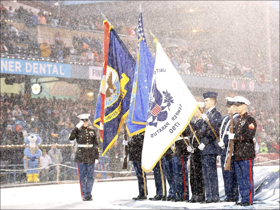 Master Sergeant Steven Kosinski, USMC, salutes the flags in the Color Guard before The Walleye's takes-on The Komets the last day of Winterfest at Fifth Third Field on January 4, 2015.