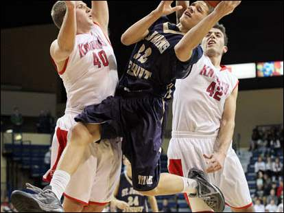 St. John's Aaron Thompson (22) shoots against  St. Francis' Jacob Lang (40) and Jeremy Eid (42).