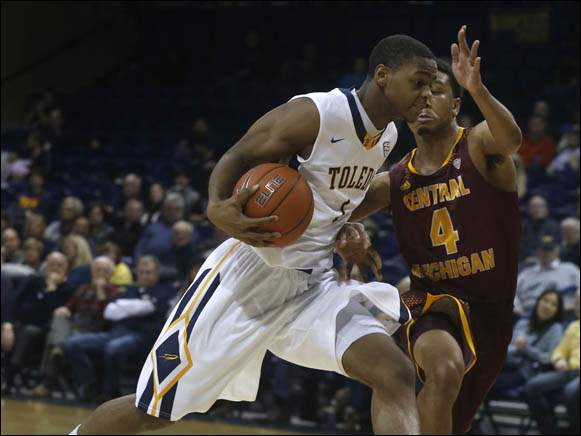 Toledo's Jonathan Williams is guarded by Central Michigan's Rayshawn Simmons.