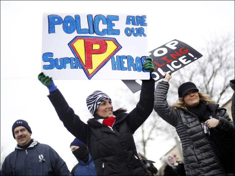 Erin Westfall, left, and Danielle Dressel, right, hold signs while they walk during a March to Support Law Enforcement.